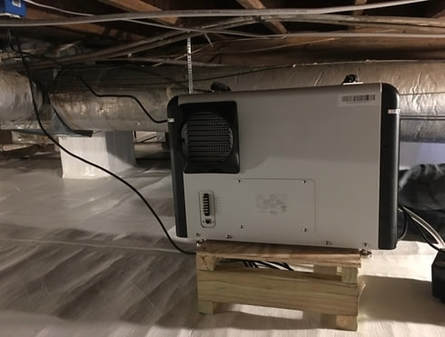 Crawl space dehumidification system with white dehumidifier sitting on wooden box